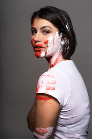 Beautiful brunette girl wearing a white t-shirt stained with paint touches her face and neck with her hand. Handprint of the palm and strokes of paint on her face. Conceptual, fashion design Фото со стока