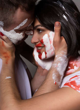 Beautiful couple of artists wearing jeans and white t-shirts soiled with white and red paint sensually hug each other on gray. Palm prints painted on their faces. Conceptual, fashion design. Close up.