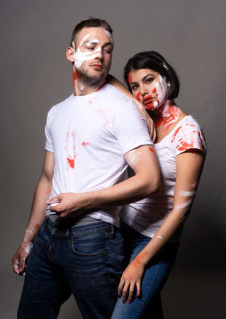 Beautiful couple of artists wearing jeans and white t-shirts soiled with white and red paint posing on gray. Palm prints painted on their faces. Conceptual, fashion, lifestyle design. Copy space.