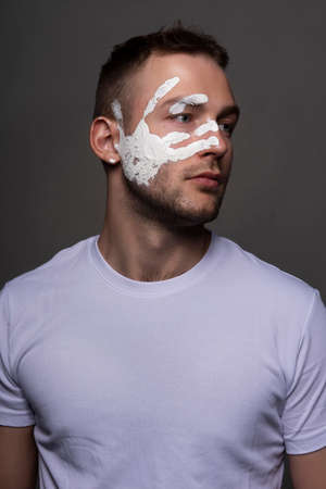 Stylish athletic male artist wearing a white t-shirt stained with red paint posing on gray background. White handprint of the palm on his face. Conceptual, fashion design. Copy space. Close up.