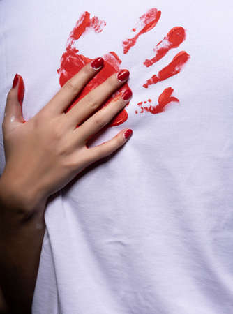 Red palm print on white cloth and beautiful female hand with red manicure. Conceptual, advertising and commercial design. Close up portrait. Copy space. Фото со стока