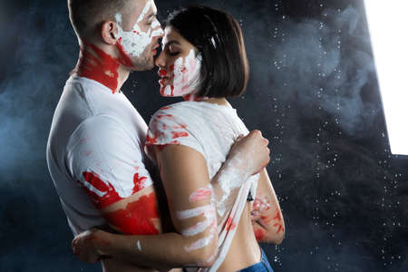 Couple of artists wearing jeans and t-shirts soiled with paint sensually hug each other under rain in smoke on black background. Palm prints painted on their faces. Concept, fashion design. Copy space