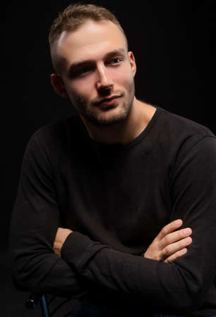 Closeup portrait of a stylish young man with a stubble on his face wearing a black jacket. Fashionable, advertising and commercial design. Copy space.