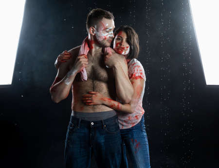 Couple of artists wearing jeans and t-shirts soiled with paint hug each other under rain in smoke on black background. Palm prints and paints on their faces. Man with naked torso. Copy space