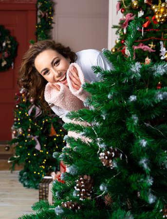 A beautiful smiling girl wearing a warm fluffy robe looks out from behind a Christmas tree decorated with garlands. New year, xmas, lifestyle design. Copy space. Фото со стока