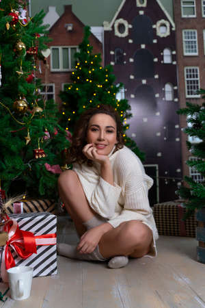A beautiful smiling girl wearing a white sweater sits in the floor among Christmas firs decorated with garlands, and xmas gifts. New year, advertising, lifestyle design. Copy space.