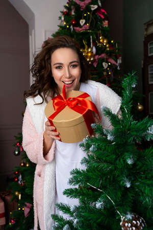 A beautiful girl wearing a white sweater stands among Christmas firs decorated with garlands, smiling joyfully with a xmas present in her hands. New year,  lifestyle design. Copy space.