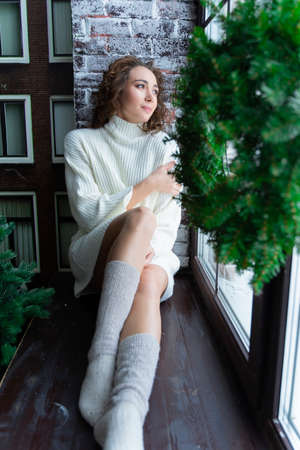 A beautiful girl wearing a white sweater and warm socks sits on the windowsill at the Christmas tree, at a window, behind which is a snow-covered street. New year, xmas, lifestyle design. Copy space.