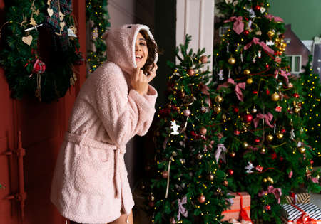 Beautiful smiling girl wearing a warm fluffy robe, wearing a hood over her head, stands at the red door decorated with fir branches and a Christmas tree. New year, xmas, lifestyle design. Copy space. Фото со стока
