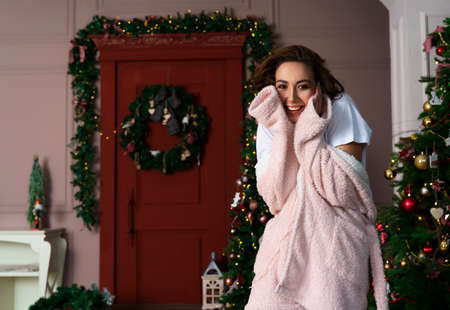A beautiful girl wearing a warm fluffy bathrobe is smiling next to a Christmas tree decorated with garlands. Фото со стока