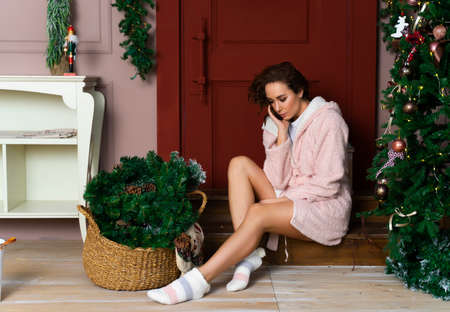 Beautiful smiling girl in a warm fluffy robe, wearing a hood over his head, sitting near the red door decorated with fir branches and Christmas tree.