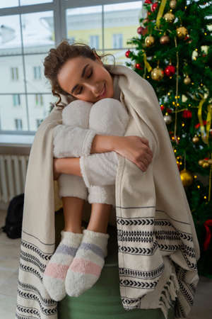 Beautiful smiling girl in a white sweater and warm socks sits wrapped in a warm blanket on a decorated Christmas tree and window behind which there is a cold snowy street. Фото со стока