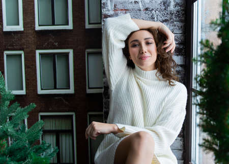 Beautiful girl in a white sweater and warm socks sitting on a windowsill at the Christmas tree by the window, behind which stands the snowy street. Фото со стока