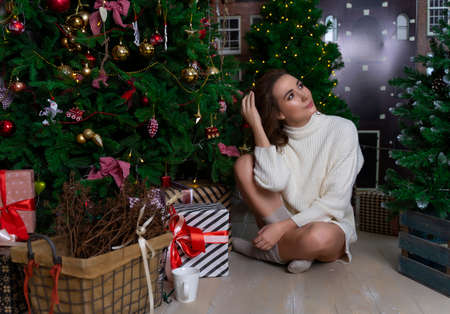 Beautiful smiling girl in a white sweater sits in the floor among Christmas trees, decorated with garlands, and gifts. Фото со стока