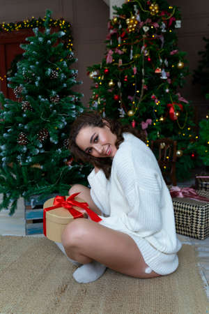 A beautiful girl in a white sweater is sitting among Christmas trees decorated with garlands, smiling happily with a gift in her hands.