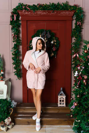 A beautiful smiling girl in a warm fluffy robe, dressed in a hood on her head, stands near the red door, decorated with fir branches and a Christmas tree. Фото со стока