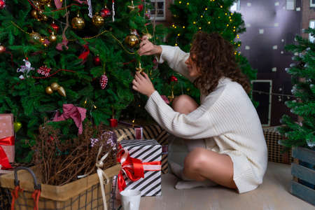A beautiful girl in a white sweater is sitting among Christmas trees with garlands, smiling joyfully, decorating a fir tree.