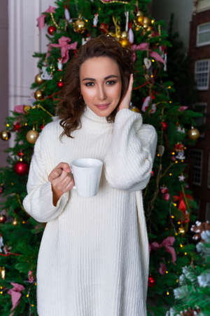A beautiful girl dressed in a white sweater is standing among Christmas trees decorated with garlands, smiling joyfully, holding a cup of hot drink. Фото со стока
