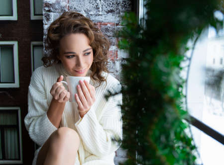 A beautiful girl in a white sweater and warm socks is sitting on the windowsill by the Christmas tree, by the window, behind which stands a snowy street, and drinks a cup of hot drink. Фото со стока