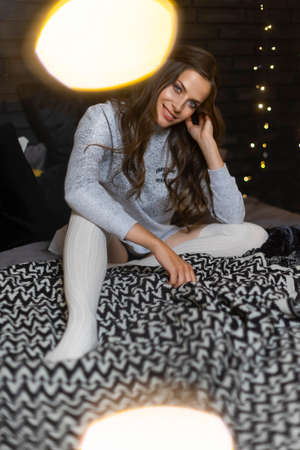 Beautiful leggy smiling girl, dressed in a sweater, panties and leggings, sits on a bed near the Christmas tree, decorated with garlands, light bulbs. New year, lifestyle design. Copy space. Фото со стока