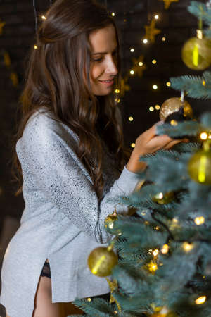 A beautiful, leggy, smiling girl, dressed in a sweater, panties and leggings, adorns the Christmas tree with garlands, light bulbs and gold balls. New year, lifestyle design. Copy space.