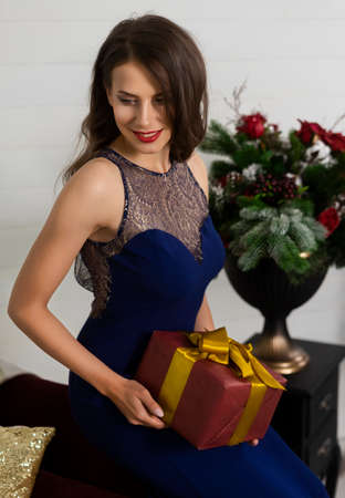 A beautiful slim smiling girl dressed in a long evening dress happily holds in her hands a Christmas present in a festive interior. New year, lifestyle, fashion design. Copy space.