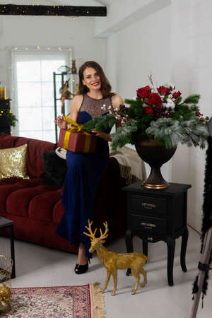 A beautiful slim smiling girl dressed in a long evening dress unpacks a Christmas gift in a festive interior. New year, lifestyle, fashion design. Copy space. Фото со стока