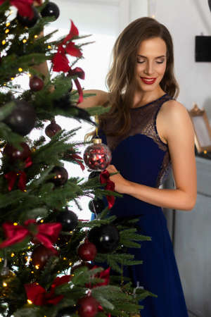 A beautiful slim smiling girl dressed in a long evening dress adorns the Christmas tree in a festive interior. New year, lifestyle, fashion design. Copy space.