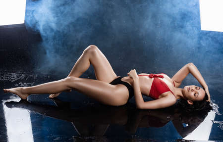 A beautiful sexy wet leggy brunette girl, dressed in black panties and a red bra, sits on the floor and sensually flexes and touches her hair under raindrops in theatrical smoke. Copy space. Фото со стока