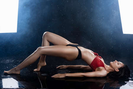 A beautiful sexy wet leggy brunette girl, dressed in black panties and a red bra, sits on the floor and sensually flexes under raindrops in theatrical smoke. Copy space. Advertising design. Фото со стока