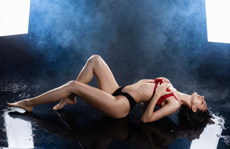 A beautiful sexy wet leggy brunette girl, dressed in black panties and a red bra, sits on the floor and sensually flexes and touches her chest under raindrops in theatrical smoke. Copy space. Фото со стока