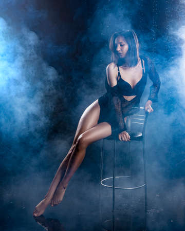 A beautiful sexy wet leggy brunette girl, dressed in black lingerie and a net cloak, sensually sits on a bar stool under raindrops in theatrical smoke. Copy space. Advertising and commercial design.