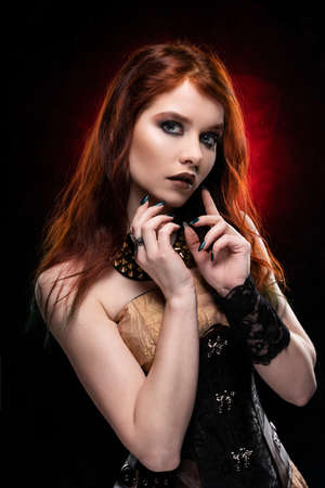 A beautiful thoughtful redhead cosplay girl wearing a Victorian-style steampunk dress and corset. Portrait. Black and red background. Copy space.