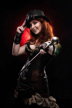 Beautiful smiling redhead cosplayer girl wearing a Victorian-style steampunk costume and hat with a big breast in a deep neckline holds cane on outstretched hand. Red and black background. Copy space.