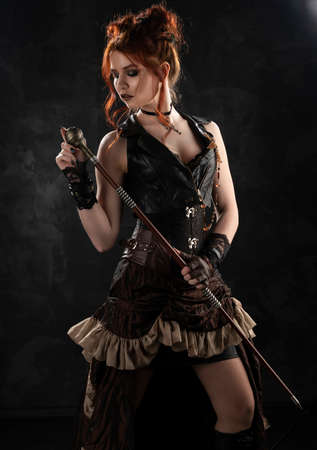 A beautiful red-haired cosplayer girl wearing a Victorian-style steampunk costume with a big breast in a deep neckline thoughtfully holds a cane in her hands on a dark background. Copy space. Foto de archivo