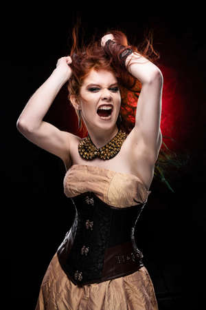 Beautiful redhead cosplayer girl wearing Victorian-style steampunk dress screams and shooks her hair with her hands. Red and black background. Copy space.