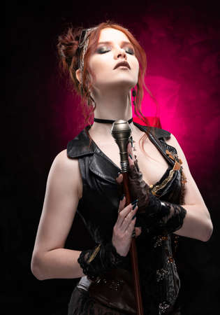 A beautiful red-haired cosplayer girl wearing a Victorian-style steampunk costume with large breasts in a deep neckline and glasses holding a cane on a black and purple background. Copy space.