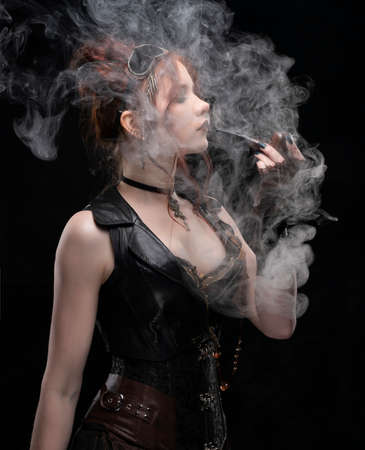 A beautiful red-haired cosplayer girl wearing a Victorian-style steampunk costume with a large breast in a deep neckline smoking a pipe in a puff of smoke  a black background. Copy space.