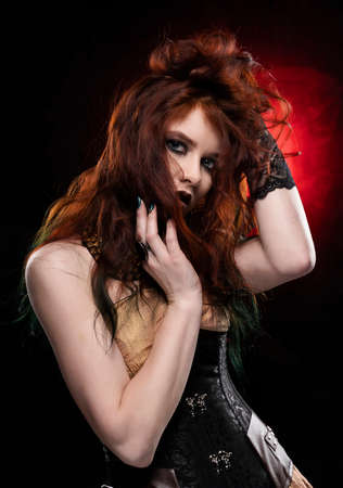 Beautiful redhead cosplayer girl wearing Victorian-style steampunk dress shooks her hair with her hands. Red and black background. Copy space.