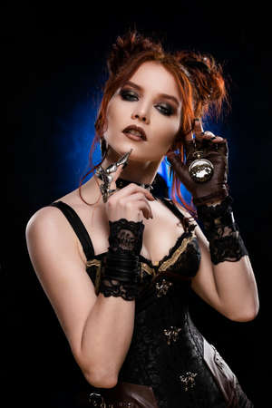Beautiful redhead cosplayer girl wearing a Victorian-style steampunk costume with a big breast in a deep neckline  is listening to a pocket watch in her hand. Blue and black background. Copy space. Фото со стока