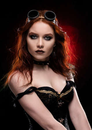 Beautiful smiling redhead cosplayer girl wearing a Victorian-style steampunk costume with a big breast in a deep neckline on red and black background. Portrait. Copy space.
