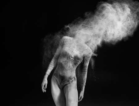 Beautiful slim girl wearing a gymnastic bodysuit covered with white powder and dust flies from her hair on a dark. Artistic conceptual black and white photo. Copy space