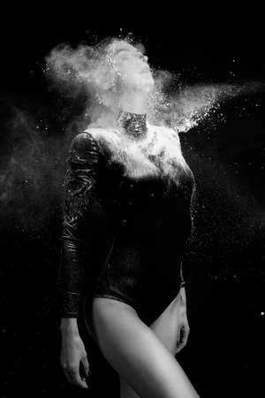 Beautiful slim girl wearing a gymnastic bodysuit covered with clouds of the flying white powder poses on a dark background. Artistic conceptual and advertising black and white photo. Copy space. Фото со стока