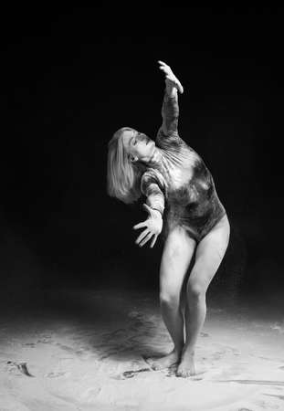 Beautiful slim girl wearing a gymnastic bodysuit covered with white powder talcum dust jumps dances on a dark. Artistic conceptual and advertising black and white photo. Copy space