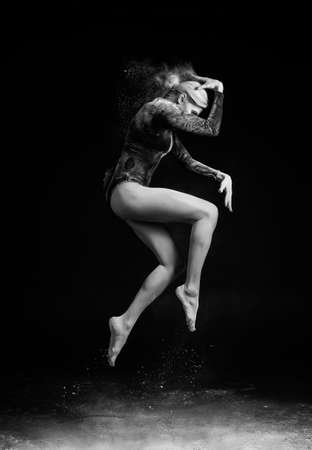 Beautiful slim girl wearing a gymnastic bodysuit covered with clouds of the flying white powder jumps dancing on a dark. Artistic conceptual and advertising black and white photo. Copy space