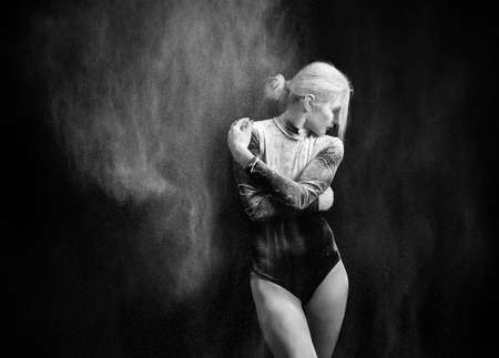 Beautiful slim girl wearing a gymnastic bodysuit covered with clouds of the flying white powder dances on a dark background. Artistic conceptual and advertising black and white photo. Copy space Фото со стока