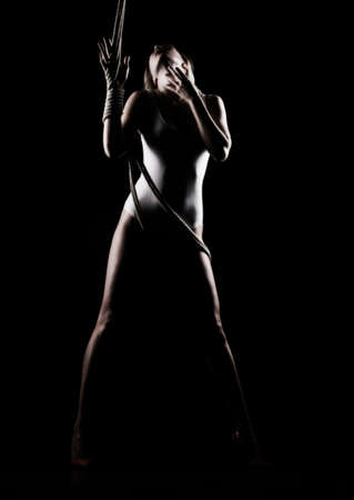 Beautiful slender blonde girl, wearing a white bodisuit and red stilettos, sensually plays and poses with the ropes. Black background. Artistic noir silhouette photo. Copy space. Фото со стока