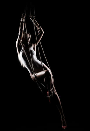Beautiful slender blonde girl, wearing a white bodisuit and red stilettos, sensually hangs and dances on the ropes. Black background. Artistic noir silhouette photo. Copy space.