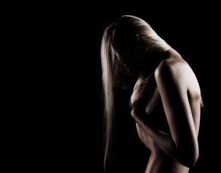 Beautiful slim topless blonde girl with hair falling on her face, stands sideways with a her hand covering her big boobs. Black background. Artistic noir silhouette photo. Copy space.