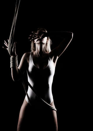 Beautiful slender blonde girl with big breast and nipples appearing through clothes, wearing a white bodisuit, sensually plays with the ropes on black. Artistic noir silhouette photo. Copy space.